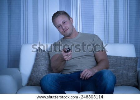 Man Relaxing On Sofa And Holding Tv Remote Control - stock photo