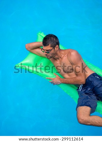 man relaxing on the air bed in the swimming pool.  vacation and free time - stock photo