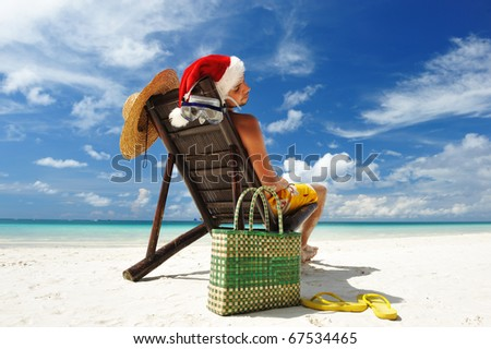 Man relaxing on the beach in santa's hat - stock photo
