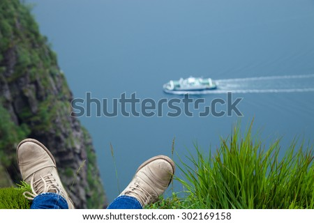 Man relaxing on the edge of tall fjord in Norway - nature and travel background. - stock photo