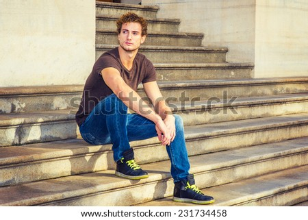 Man Relaxing Outside. Wearing dark brown T shirt, blue jeans, black sneakers, a young sexy guy with curly hair is sitting on stairs outside office, confidently looking forward. - stock photo
