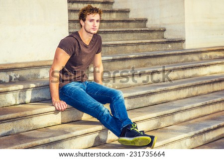 Man Relaxing Outside. Wearing dark brown T shirt, blue jeans, black sneakers, a young sexy guy with curly hair is sitting on stairs outside office, stretching legs, crossing, thinking. - stock photo
