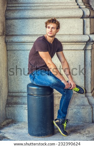 Man Relaxing Outside. Wearing dark brown T shirt, blue jeans, black sneakers, a young sexy guy with curly hair is sitting on a metal stake on the corner, crossing leg, looking around, waiting for you. - stock photo