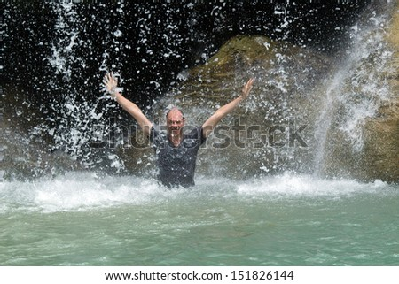 Man relaxing under tropical Erawan waterfall, Thailand