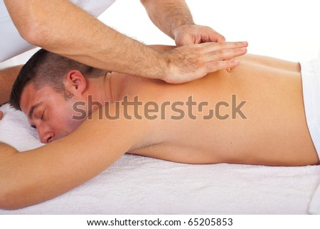 Man relaxing with a back massage at spa retreat - stock photo