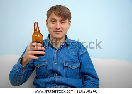 Man relaxing with a bottle of beer at home - stock photo