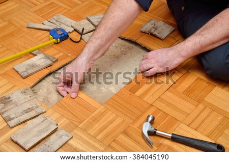 Man removing damaged pieces of wooden parquet