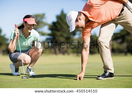 Man removing golf ball from hole while woman crouching on field