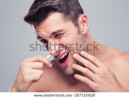 Man removing nose hair with tweezers over gray background - stock photo