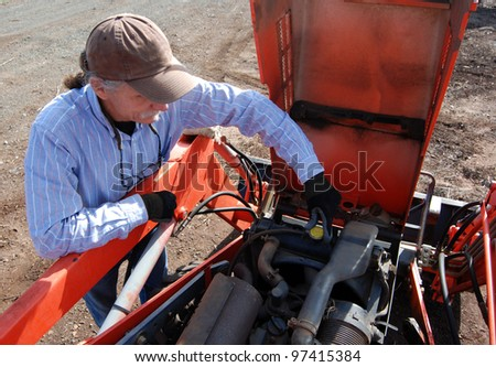 Man removing radiator cap on tractor while conducting an annual tune up, maintenance on the tractor. - stock photo