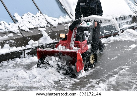 Man Removing Snow with a Snow Blower - stock photo