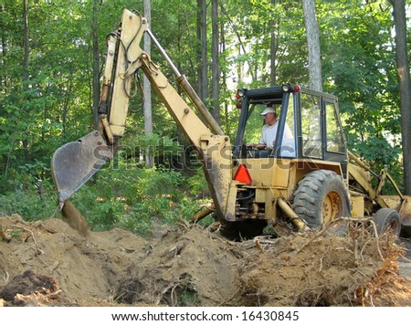 Man removing tree roots with a backhoe