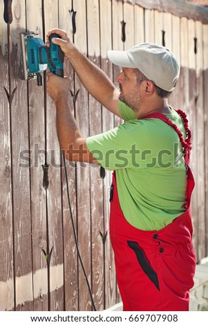 Man renewing a wooden fence - sanding away the old paint coat