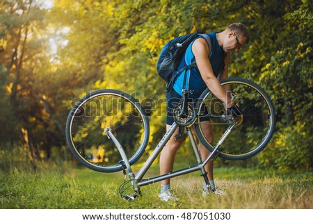 man repair his bicycle in the forest