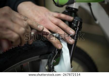 man repairing a bike with a screwdriver - stock photo