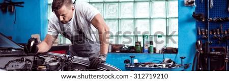 Man repairing a car in the garage - stock photo