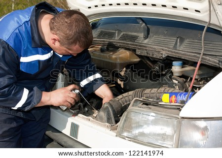 man repairing a car with a raised soot - stock photo