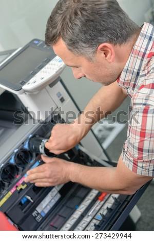 Man repairing a printer - stock photo