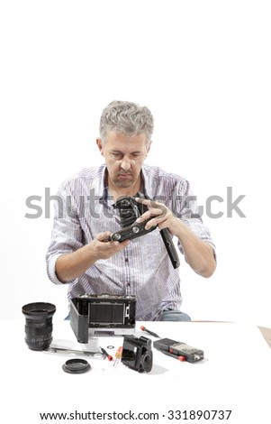 Man repairing an old camera Male repairing an old camera at his workplace on white background