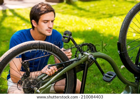 Man repairing his bike. Confident young man fixing his bike while kneeling on grass