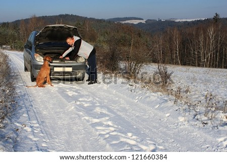 man repairing the car on a deserted road, winter weather - stock photo