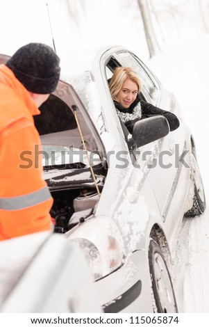 Man repairing woman's car snow assistance winter broken tools mechanic - stock photo