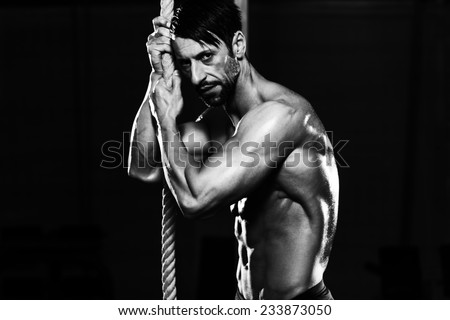 Man Resting After Fitness Rope Climb Exercise In Fitness Gym Workout - stock photo