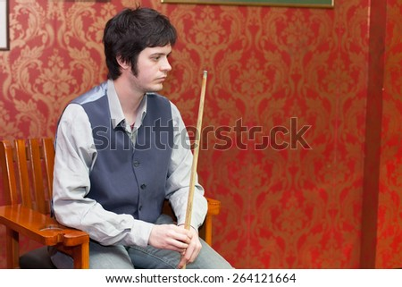 man resting during snooker game - stock photo
