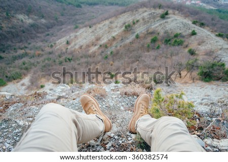Man resting in the mountains, view of legs. Point of view shot
