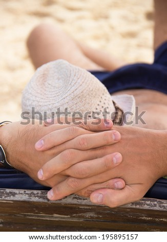 man resting on a sun lounger on the beach