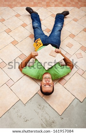 Man resting on ceramic floor tiles - taking a short break - stock photo
