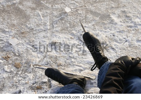 man resting on ice with focus on skates - stock photo