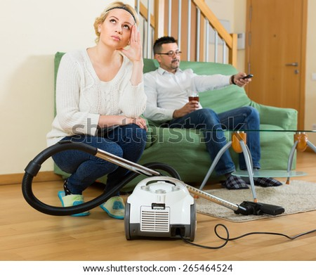 Man resting on sofa with beverage, his sad wife cleaning around. Focus on woman - stock photo
