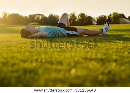 Man resting on the grass after a marathon. Guy lying in the park at sunset. - stock photo
