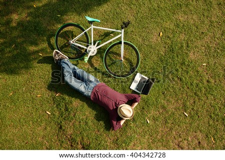 Man resting on the ground with laptop and bicycle next to him - stock photo