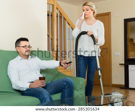 Man resting with beverage, his sad wife cleaning around. Focus on man - stock photo