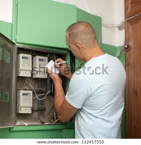 Man rewrites the electrical meter readings - stock photo