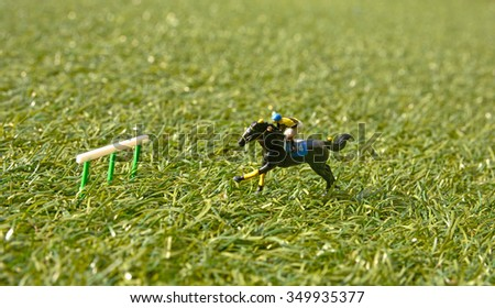 man ride horse jump over barrier on lawn, model figure