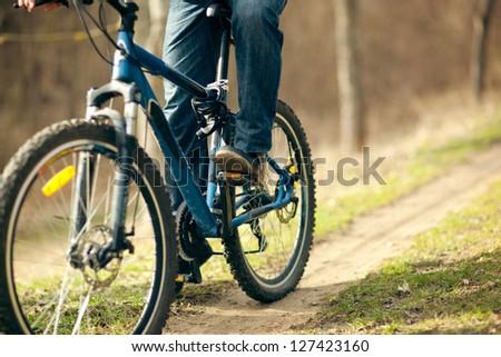 man rides a bicycle on mountain roads, photo closeup - stock photo