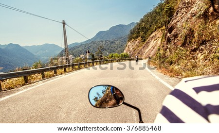 man rides a motorcycle along the serpentine in the mountains, the view of the mountains of Vietnam. - stock photo