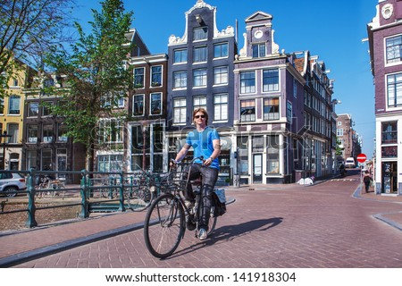 Man riding a bicycle in historical part of Amsterdam - stock photo