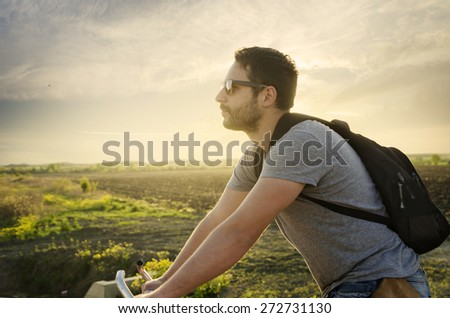 Man riding a bicycle in nature at sunset - stock photo