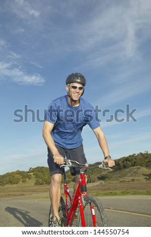 Man riding a bicycle on a road - stock photo