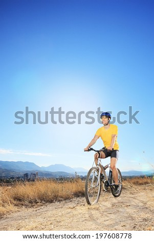 Man riding a bike in a field with the sky in the background - stock photo
