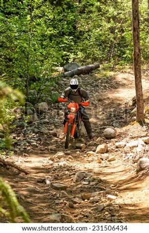 Man riding a dirt bike along a rocky trail deep in the wilderness - stock photo