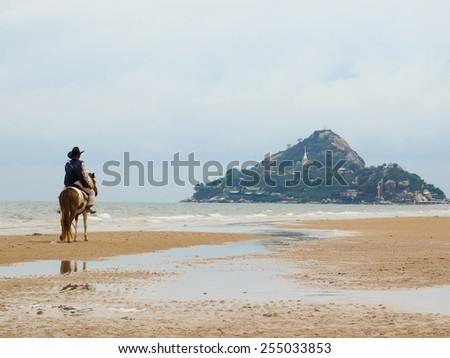 MAN RIDING A HORSE ON THE BEACH