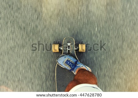 Man riding a longboard, a plan view on the move, close-up, first-person view. Lens, flare effect - stock photo