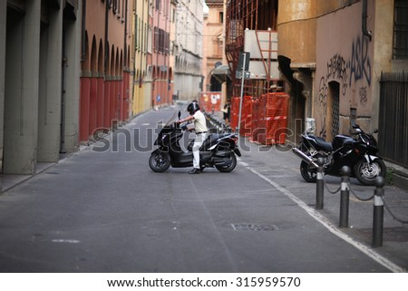 Man riding a motorcycle down the street In Italy