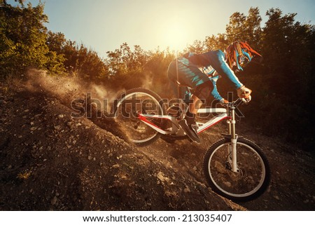 Man riding a mountain bike in downhill style at sunrise. Extreme sports on a bicycle.