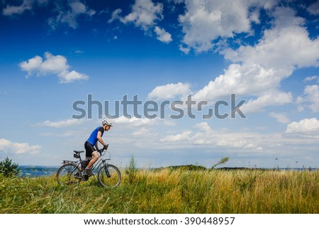 Man riding a mountain bike up the beautiful nature . Traveling by bicycle. Sports lifestyle